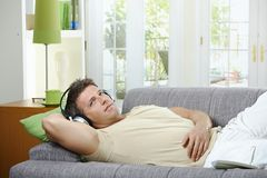 Man on sofa listening to music smiling Stock Image