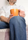 Man on a sofa with a pot of coffee Stock Images