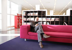 Man on sofa reading Royalty Free Stock Photography