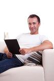 Man on the sofa reading a book Royalty Free Stock Images