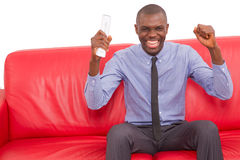 Man on the sofa with remote control rejoice. Man smiling on the sofa with remote control rejoice Royalty Free Stock Photography