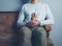 Man on sofa with strange potato Stock Image