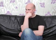 Man sofa thinking shocked Stock Images