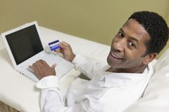 Man on sofa  Using Credit Card to Make Purchase with Laptop portrait high angle view Stock Photo
