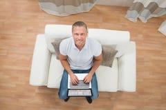 Man On Sofa Using Laptop Stock Photography