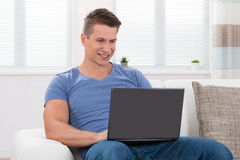 Man On Sofa Using Laptop Stock Images