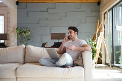 Man on sofa using phone and laptop. Smiling handsome man on sofa sitting with laptop while talking on phone Stock Photos
