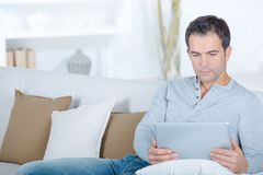 Man on sofa using tablet. Man Stock Photography