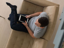 Man on sofa using tablet computer Stock Photos
