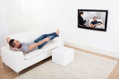 Man on sofa watching tv Stock Image