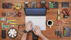Man software engineer working with a laptop and an external hard drive. Wooden table top view. Download files and stock footage