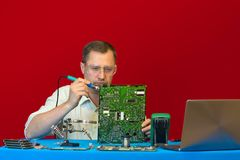 A man soldering electronic circuit. Engineer service center repairs the power supply LCD TV. stock image