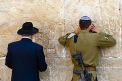 A man and a soldier pray at the Western Wall stock photos