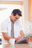 Man solving crossword puzzle in the kitchen Stock Image
