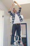 Man som ändrar en lightbulb i vardagsrum royaltyfria foton