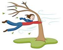 Man som är hållande på till trädet på Windy Day Royaltyfri Fotografi