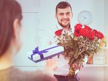 Man som är klar att framlägga blommor och gåvan på ferie fotografering för bildbyråer