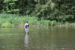 Man som är upptagen med flyfishing Arkivfoto
