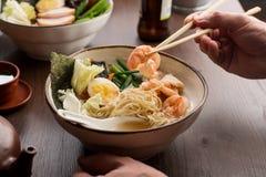 Man som äter asiatiska ramen med räkor och nudlar i en restaurang royaltyfri bild