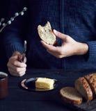 Man som äter bröd med smör royaltyfri bild