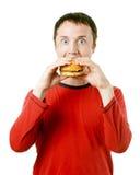 Man som äter en hamburgare Fotografering för Bildbyråer