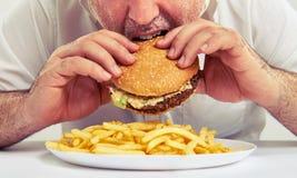 Man som äter hamburgare- och fransmansmåfiskar Royaltyfri Foto