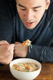 Man som äter hemlagad feg soppa royaltyfria bilder