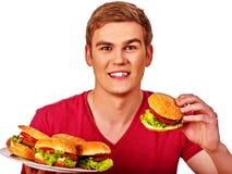 Man som äter stora hamburgare Royaltyfria Foton