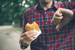 Man som öppnar en hamburgare Royaltyfria Foton