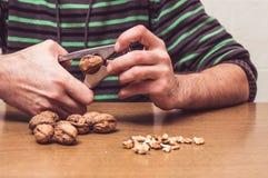 Man som öppnar några valnötter på en tabell Royaltyfri Fotografi