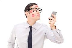 Man som överför en kyss till och med en mobiltelefon Arkivfoto