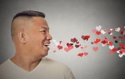 Man som överför kyssar, röda hjärtor som kommer ut ur öppen mun arkivbild