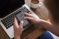 Man som överför textmeddelandet på mobiltelefonstund genom att använda bärbara datorn Arkivbild