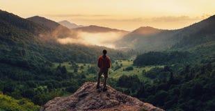 Man som överst står av klippan på solnedgången arkivfoto