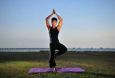 man som 5 utför yoga Arkivfoto