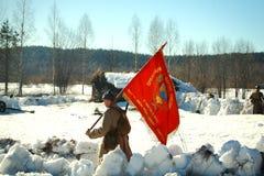 Man som agerar den sovjetiska soldaten Bearing för WWII ett rött baner Royaltyfri Fotografi