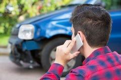 Man som anmäler bilkrasch på mobiltelefonen Royaltyfri Fotografi