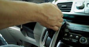 Man som använder överföringen och använder styrninghjulet styrning automatisk och strömbrytarekugghjul Slut upp av kugghjulf?rskj lager videofilmer