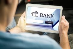 Man som använder applikation för mobil bank med minnestavlan royaltyfri fotografi