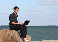 Man som använder bärbar dator och telefonen på stranden Arkivbild