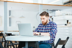 Man som använder bärbar datordatoren i kafé Royaltyfri Bild