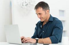 Man som använder bärbara datorn arkivfoto