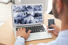 Man som använder bärbara datorn för att övervaka CCTV-kameror arkivbild