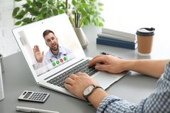 Man som anv?nder b?rbara datorn f?r online-konsultation med doktorn via video pratstund p? tabellen royaltyfri bild