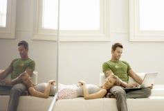 Man som använder bärbara datorn med kvinnan som ligger på hans varv arkivfoto
