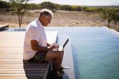 Man som använder bärbara datorn nära poolside Arkivbilder