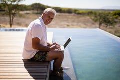 Man som använder bärbara datorn nära poolside under safarisemester Royaltyfri Foto