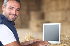 Man som använder bärbara datorn på en lantgård arkivbild