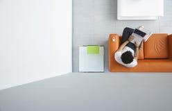 Man som använder bärbara datorn på orange Sofa At Office Fotografering för Bildbyråer