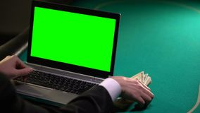 Man som använder bärbara datorn på pokertabellen som tjänar pengar i online-slå vad, dobbleri stock video